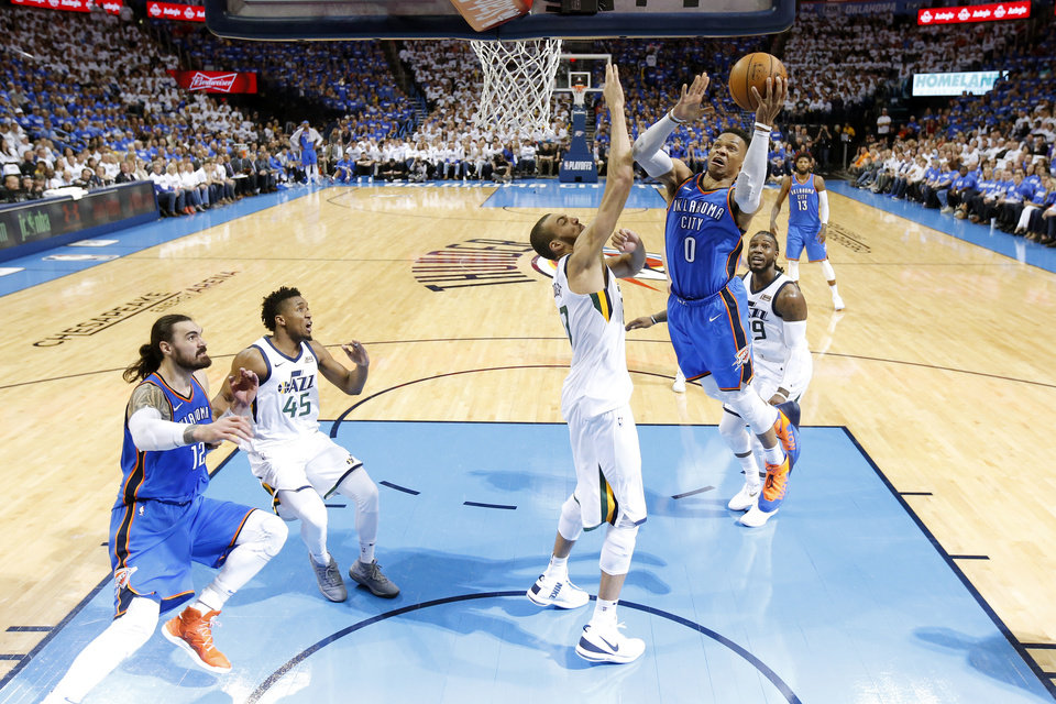 Photo - Oklahoma City's Russell Westbrook (0) goes to the basket beside Utah's Rudy Gobert (27) during Game 5 of the first round NBA playoff series between the Oklahoma City Thunder and the Utah Jazz at Chesapeake Energy Arena in Oklahoma City, Wednesday, April 25, 2018. OKC Thunder won 107-99. Photo by Bryan Terry, The Oklahoman