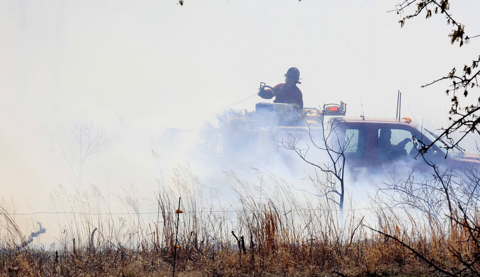 Photo - A firefighter on a brush pumper in a field at NE 73 Street and Post Road to deal with a grass fire fueled by dead tree limbs from previous ice storms in Oklahoma City Wednesday, April 6, 2011. Photo by Paul B. Southerland, The Oklahoman