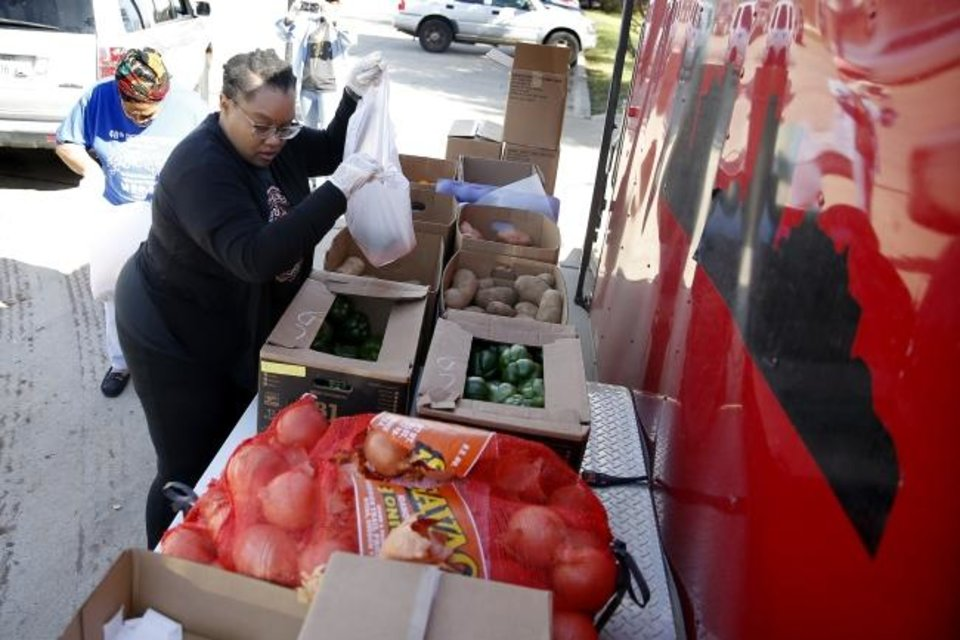 Photo -  Jennifer Prince helps bag food for families at a drive-thru food distribution for Oklahoma City school students outside The Market at Restore OKC. The drive-thru food distribution was set up at Restore OKC, 2222 NE 27, in partnership with Skyline Urban Ministry. [Bryan Terry/The Oklahoman]
