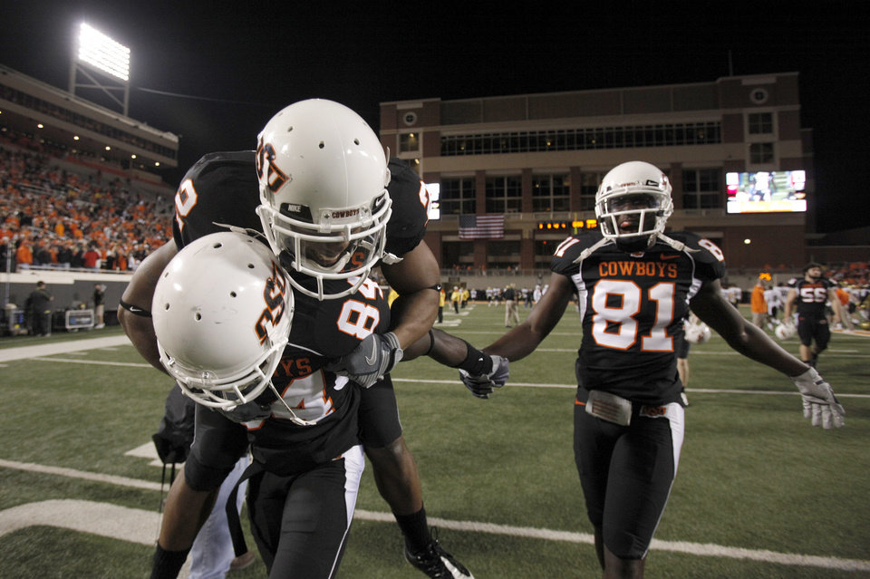 Photo - OSU's Hubert Anyiam (84), Beau Johnson (2) and Justin Blackmon (81) celebrate their win following the college football game between Oklahoma State University (OSU) and the University of Colorado (CU) at Boone Pickens Stadium in Stillwater, Okla., Thursday, Nov. 19, 2009. Photo by Sarah Phipps, The Oklahoman