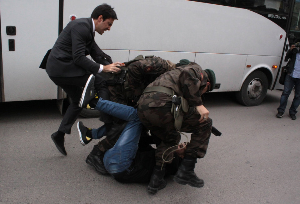Photo - In this photo taken Wednesday, May 14, 2014  a person identified by Turkish media as Yusuf Yerkel, advisor to Turkish Prime Minister Recep Tayyip Erdogan, kicks a protester already held by special forces police members during Erdogan's visiting  Soma, Turkey. Erdogan was visiting the western Turkish mining town of Soma after Turkey's worst mining accident . AP Photo/Depo Photos) TURKEY OUT  ONLINE OUT