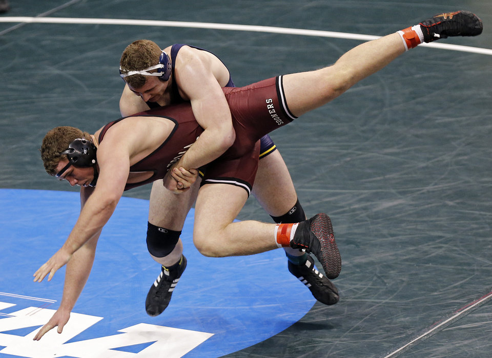 Photo - Oklahoma's Ross Larson is taken down by Michigan's Adam Coon in the 285 pound match during the 2014 NCAA Div. 1 Wrestling Championships at Chesapeake Energy Arena in Oklahoma City, Okla. on Thursday, March 20, 2014. Photo by Chris Landsberger, The Oklahoman