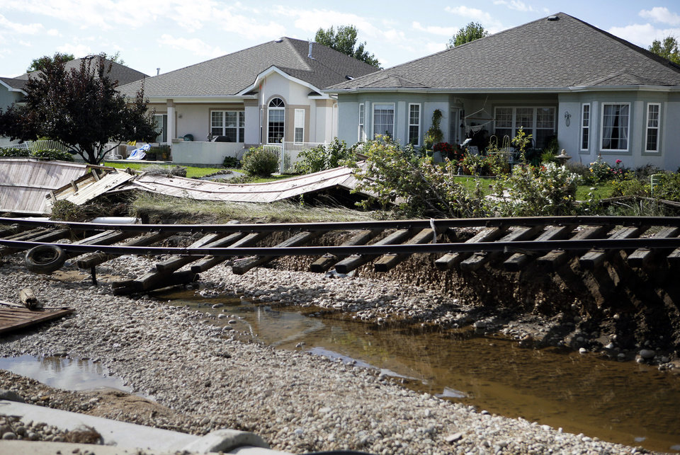 Photo - Railroad tracks are undercut by flooding in Longmont, Colo., on Thursday, Sept. 19, 2013. Rescuers continued efforts to reach stranded victims, while electricity and phone services were being restored to ravaged areas, allowing residents to contact family, friends or authorities. (AP Photo/Ed Andrieski)