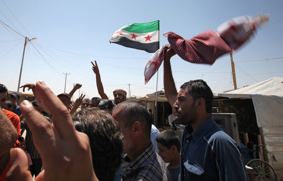 Photo - Syrian refugees chants anti-President Bashar Assad slogans and demand an international military strike on the Syrian regime at Zaatari Syrian refugee camp, in Mafraq, Jordan, Wednesday, Aug. 28, 2013. A week after the purported chemical attack on rebel-held areas outside Damascus, momentum has been building for a possible strike by the U.S. and its allies against the regime of Syrian President Bashar Assad.(AP Photo/Mohammad Hannon)
