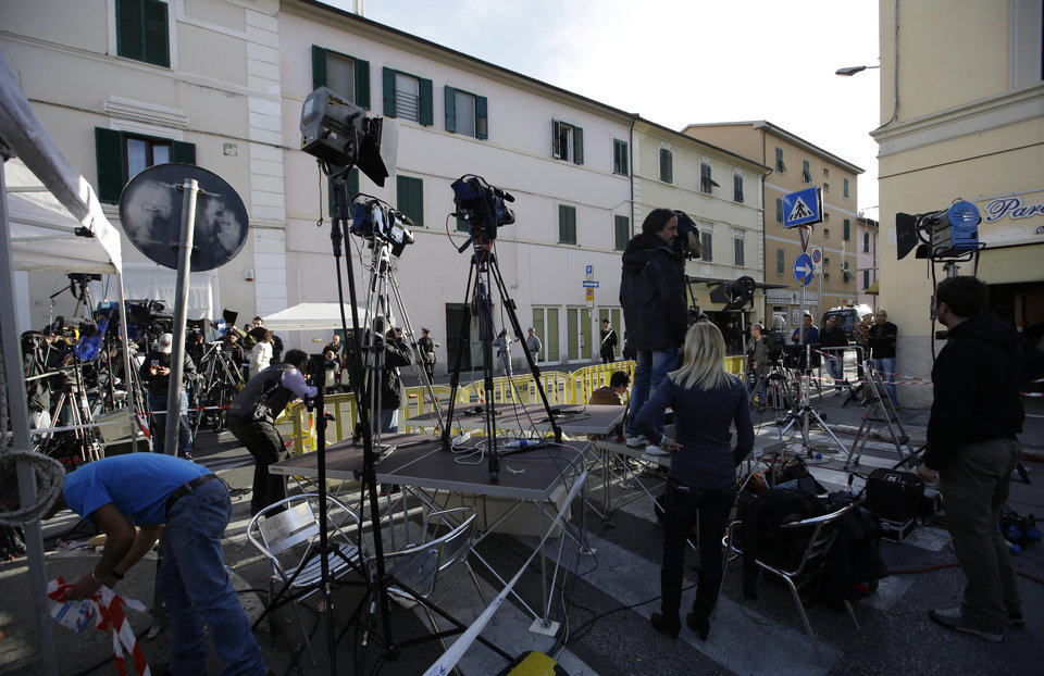 Photo -   Journalist prepare their equipment in front of the Teatro Moderno theater where the first hearing of the trial for the Jan. 13, 2012 tragedy, where 32 people died after the luxury cruise Costa Concordia was forced to evacuate some 4,200 passengers after it hit a rock while passing too close to the Giglio Island, is taking place, in Grosseto, Italy, Monday Oct. 15, 2012. (AP Photo/Gregorio Borgia)