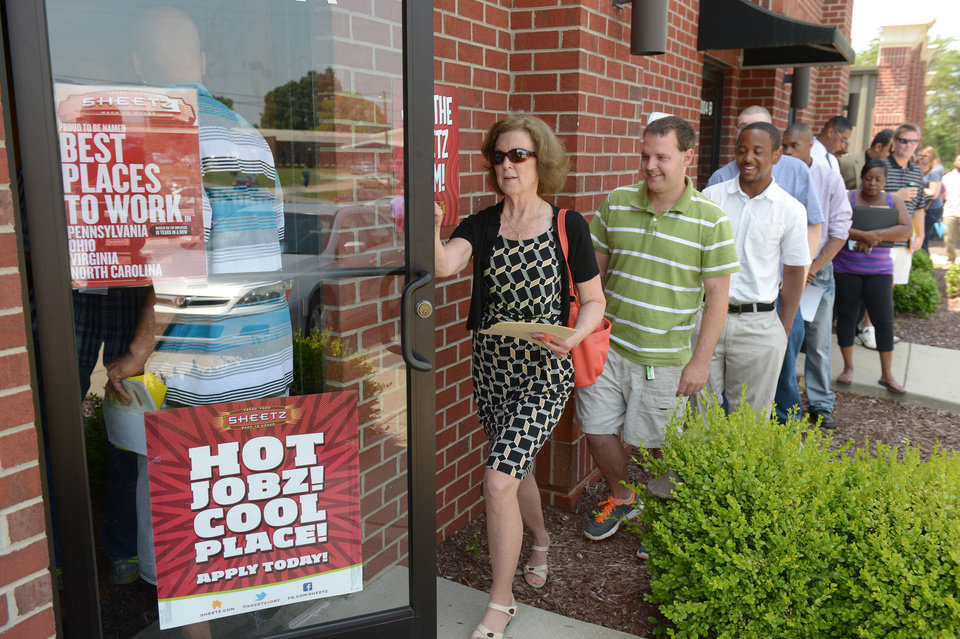 Photo - FILE - In this Wednesday, June 18, 2014 photo, job seekers attend a job fair held by Sheetz to staff their under-construction distribution center, in Burlington, N.C.  As the economic recovery enters its sixth year, many Americans don't feel better off. (AP Photo/The Times-News, Sam Roberts)