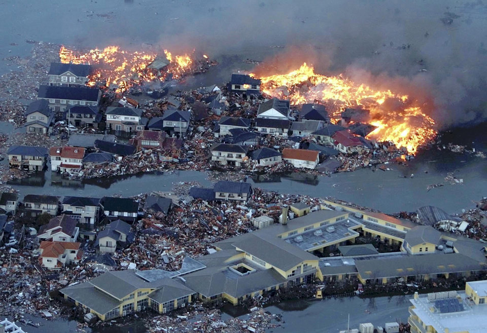 Photo - Houses are shown in flame while the Natori river floods over the surrounding area by tsunami tidal waves in Natori city, Miyagi Prefecture, northern Japan, March 11, 2011, after strong earthquakes hit the area. (AP Photo/Yasushi Kanno, The Yomiuri Shimbun)  JAPAN OUT, CREDIT MANDATORY ORG XMIT: TOK834