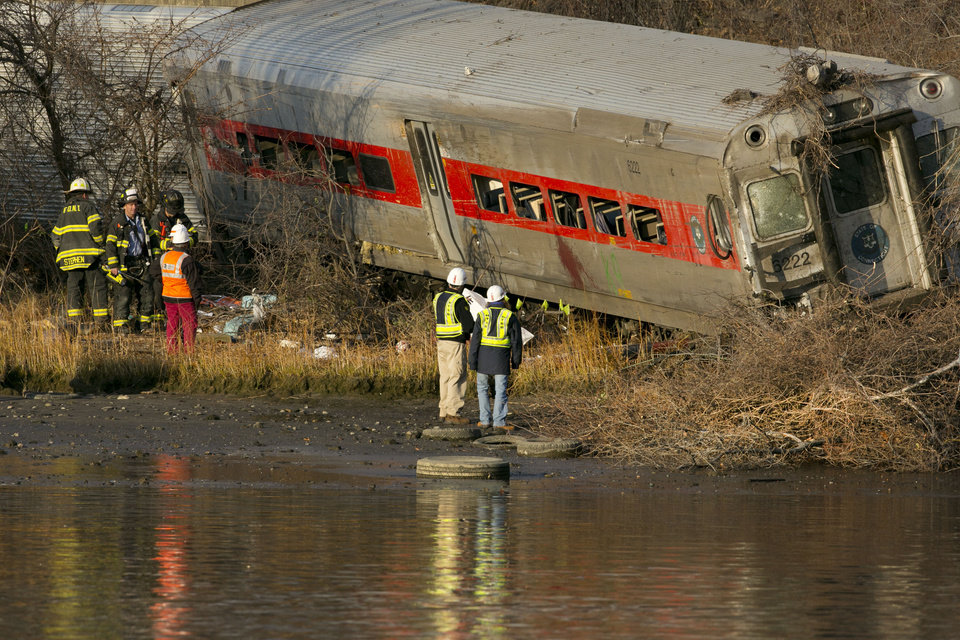 Photo - Officials with the National Transportation Safety Board inspect a derailed Metro North commuter train where it almost fell into the Harlem River, Sunday, Dec. 1, 2013 in the Bronx borough of New York. The Metro-North train derailed on a curved section of track early Sunday, coming to rest just inches from the water, killing at least four people and injuring more than 60, authorities said. (AP Photo/Mark Lennihan)
