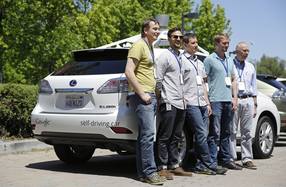 Photo - In this photo taken Wednesday, May 14, 2014, Google team members pose by a Google self-driving car at the Computer History Museum in Mountain View, Calif. From left is project direct Chris Urmson, Brian Torcellini, Dimitri Dolgov, Andrew Chatham and Ron Medford, the director of safety for the project. Four years ago, the Google team developing cars which can drive themselves became convinced that, sooner than later, the technology would be ready for the masses. There was just one problem: Driverless cars almost certainly were illegal. (AP Photo/Eric Risberg)
