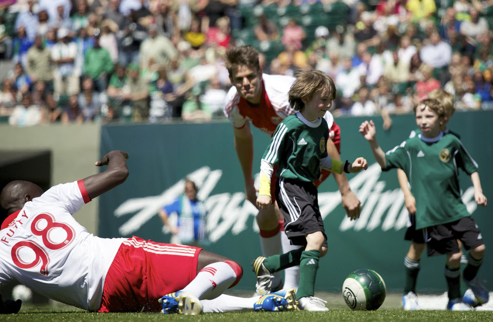 Photo - Atticus Lane-Dupre, 8, middle,  and his soccer team, The Green Machine play against the Portland Timbers soccer team in Portland, Ore., Wednesday, May 1, 2013. The Timbers and Make-A-Wish Oregon treated Atticus' team to a game at Jeld-Wen Field with more than 3,000 fans coming out to lend their support. Atticus missed the Green Machine's final match last fall because of cancer treatment. (AP Photo/The Oregonian, Bruce Ely)