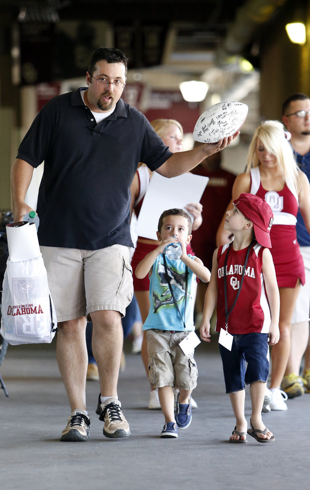 Photo - Craig Campbell, son Travis (middle) and nephew Aiden (both 5) make their way around the stadium during the Meet the Sooners event inside Gaylord Family/Oklahoma Memorial Stadium at the University of Oklahoma on Saturday, Aug. 4, 2012, in Norman, Okla.  Photo by Steve Sisney, The Oklahoman