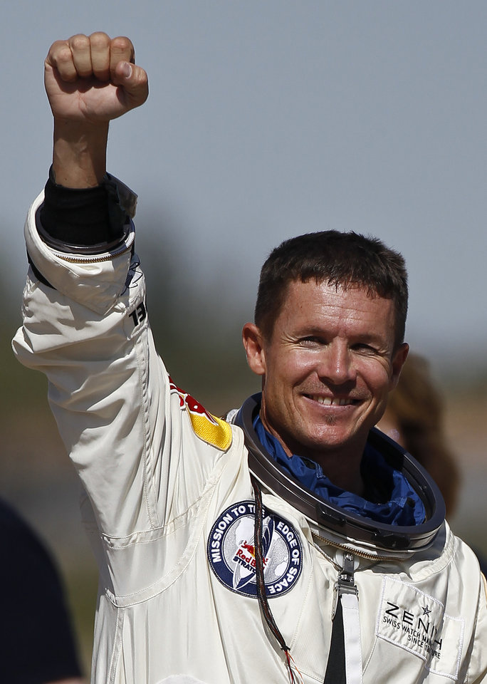 Felix Baumgartner, of Austria, pumps his fist to the crowd after successfully jumping from a space capsule lifted by a helium balloon at a height of just over 128,000 feet above the Earth's surface, Sunday, Oct. 14, 2012, in Roswell, N.M. Baumgartner came down safely in the eastern New Mexico desert minutes about nine minutes after jumping from his capsule 128,097 feet, or roughly 24 miles, above Earth (AP Photo/Ross D. Franklin) ORG XMIT: NMRF118