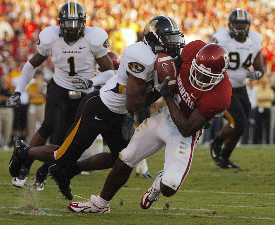 Photo - Oklahoma's Malcolm Kelly (4) is brought down after a reception by Missouri's Darnell Terrell (3) during the first half of the college football game between  the University of Oklahoma Sooners (OU) and the University of Missouri Tigers (MU) at the Gaylord Family Oklahoma Memorial Stadium on Saturday, Oct. 13, 2007, in Norman, Okla.By CHRIS LANDSBERGER, The Oklahoman