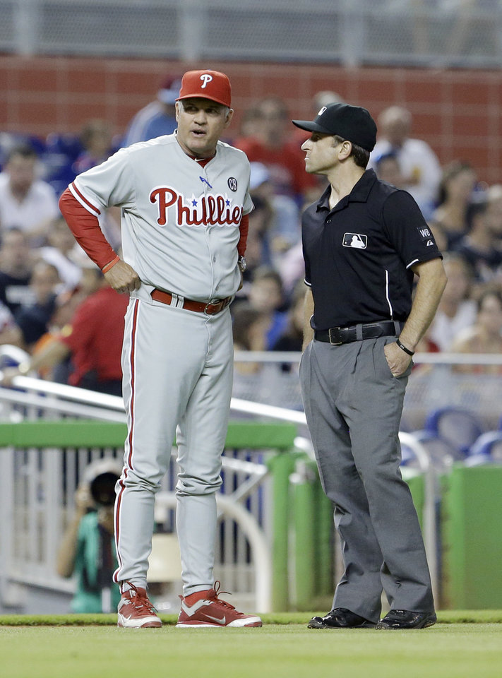 Photo - Philadelphia Phillies manager Ryne Sandberg, left, argues a call with third base umpire Chris Guccione during the first inning of a baseball game against the Miami Marlins, Wednesday, July 2, 2014, in Miami. (AP Photo/Wilfredo Lee)