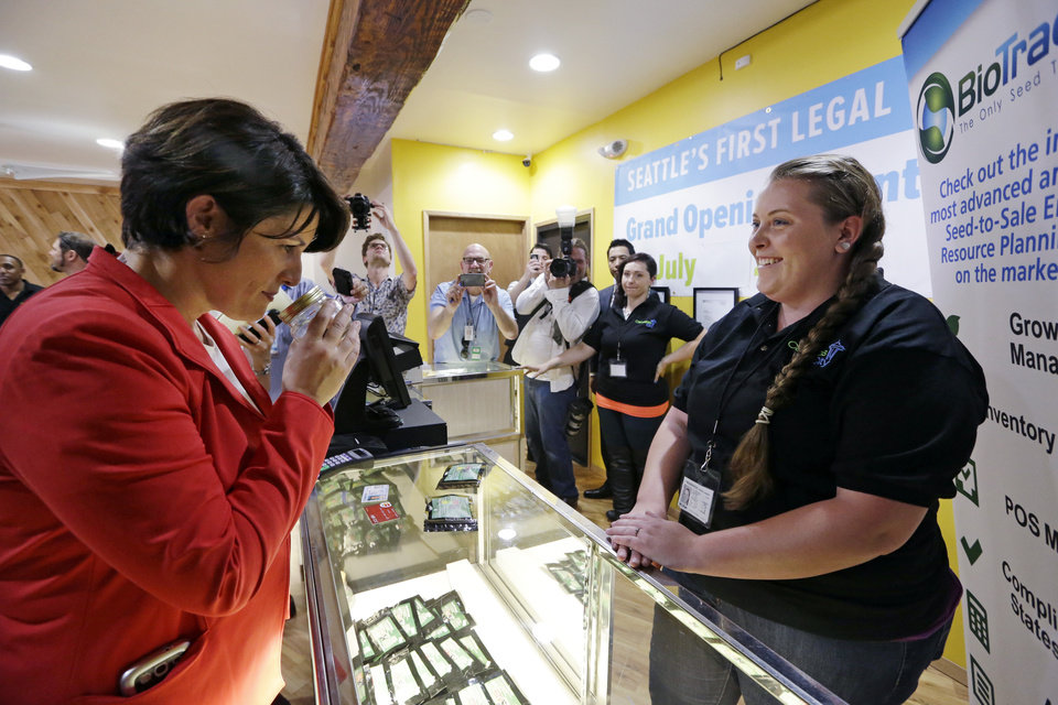 Photo - Alison Holcomb, left, criminal justice director at the Washington state ACLU, sniffs a sample of marijuana as she gets ready to make a purchase as clerk Pam Fenstermacher looks on at Cannabis City, Tuesday, July 8, 2014, in Seattle, on the first day that sales of recreational pot became legal the state.  Washington on Tuesday became the second state to allow people to buy marijuana legally in the U.S. without a doctor's note as eager customers who lined up outside stores made their purchases and savored the moment. (AP Photo/Elaine Thompson, Pool)