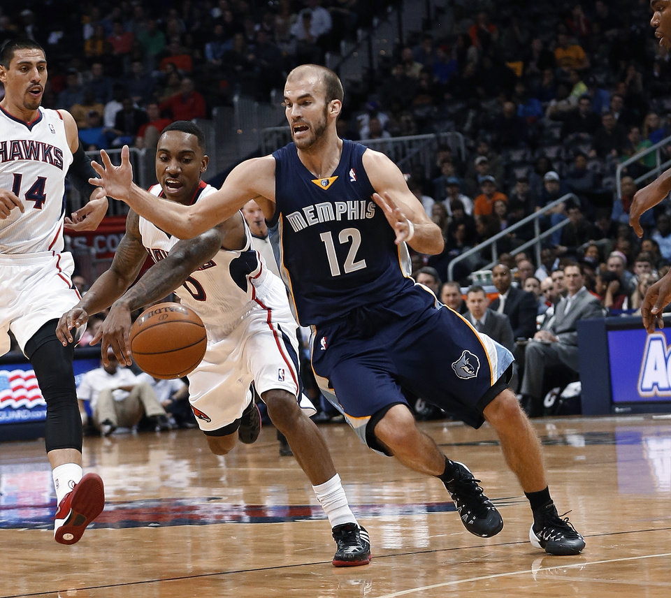 Photo - Atlanta Hawks guard Jeff Teague (0) steals the ball from Memphis Grizzlies guard Nick Calathes (12) in the second half of an NBA basketball game Saturday, Feb. 8, 2014, in Atlanta.  Memphis won 79-76. (AP Photo/John Bazemore)
