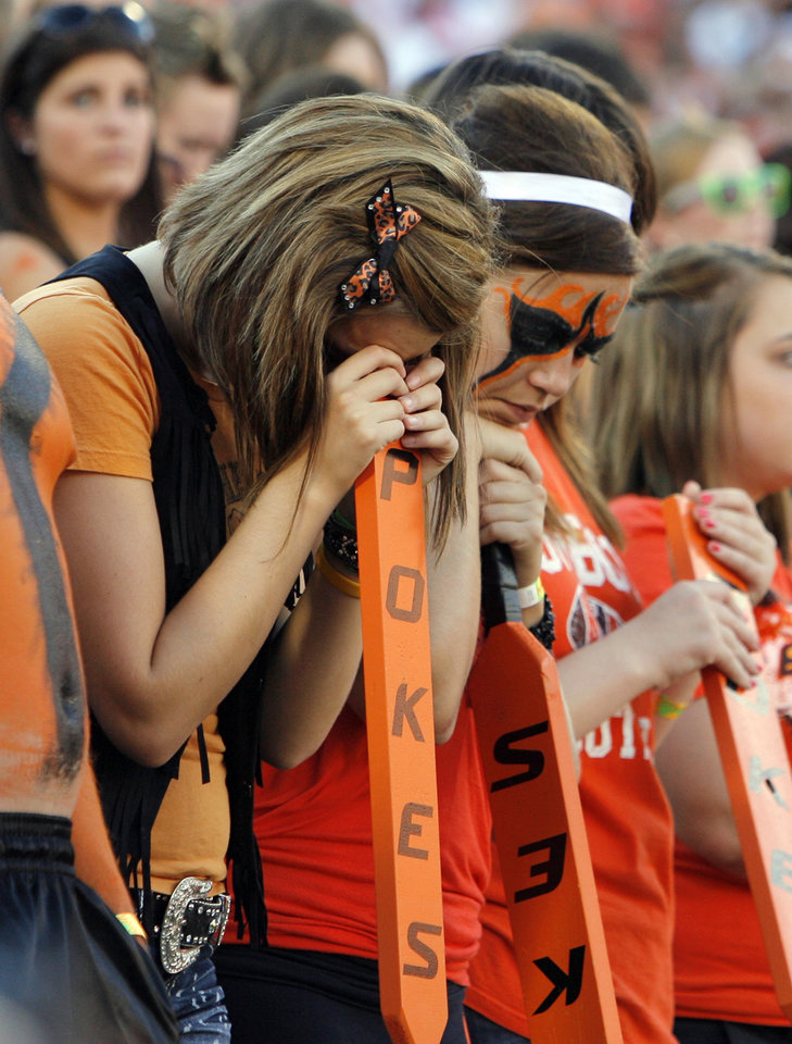 Photo - OSU fans observe a moment of silence to honor those who died in the terrorist attacks of September 11, 2001, before the college football game between the Oklahoma State University Cowboys (OSU) and the Troy University Trojans at Boone Pickens Stadium in Stillwater, Okla., Saturday, Sept. 11, 2010. Photo by Nate Billings, The Oklahoman