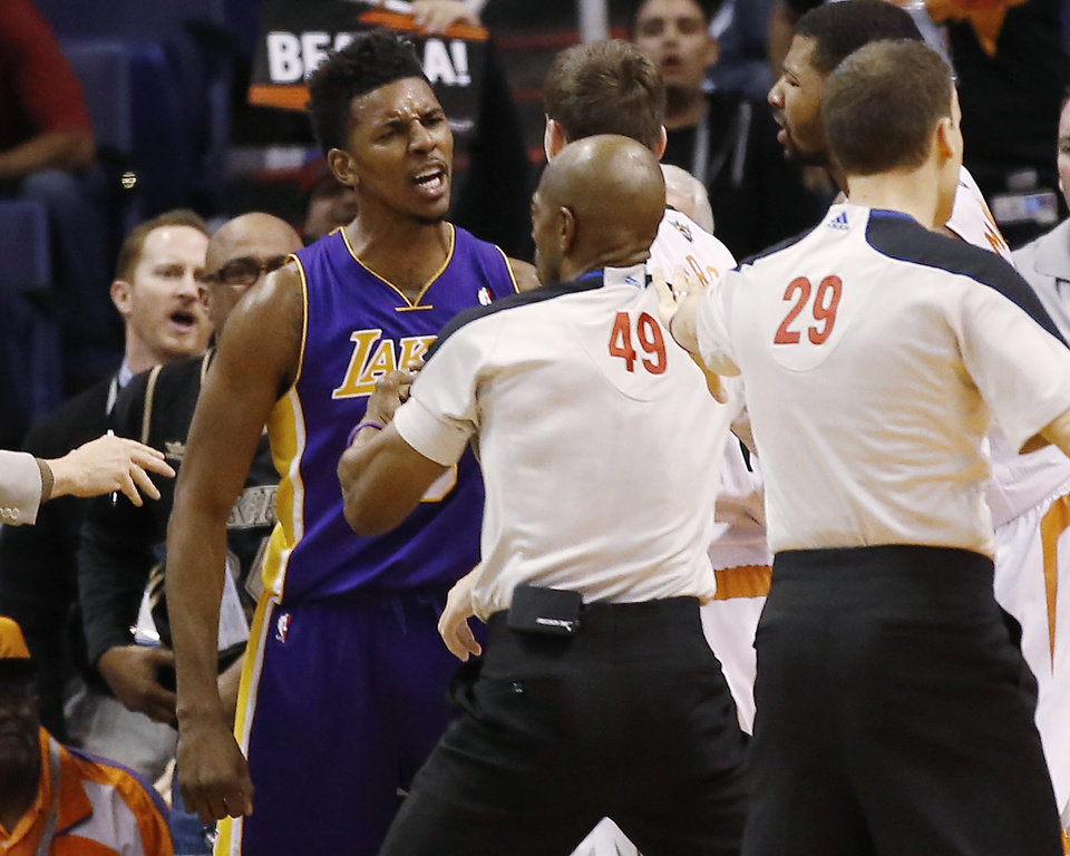 Photo - Los Angeles Lakers'Nick Young is separated from Phoenix Suns guard Goran Dragic after Young was fouled by Suns' Alex Len during the second quarter of an NBA basketball game Wednesday, Jan. 15, 2014, in Phoenix. (AP Photo/The Arizona Republic, Michael Chow) MESA OUT  MARICOPA COUNTY OUT  NO SALES