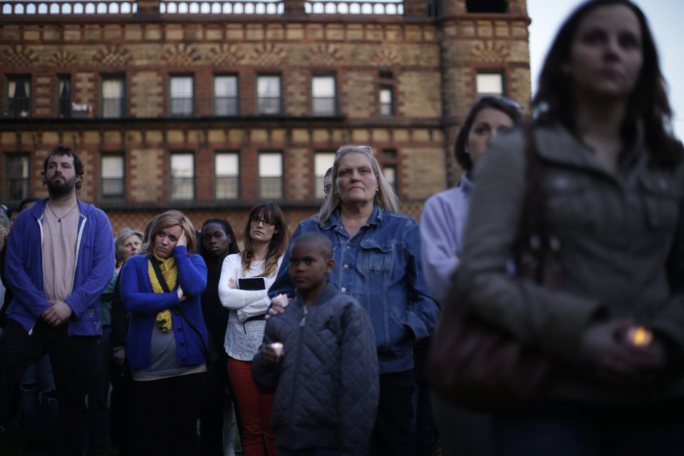 Photo - Mourners attend a candlelight vigil in the aftermath of Monday's Boston Marathon explosions, which killed at least three and injured more than 140, Wednesday, April 17, 2013, at City Hall in Cambridge, Mass. (AP Photo/Matt Rourke)