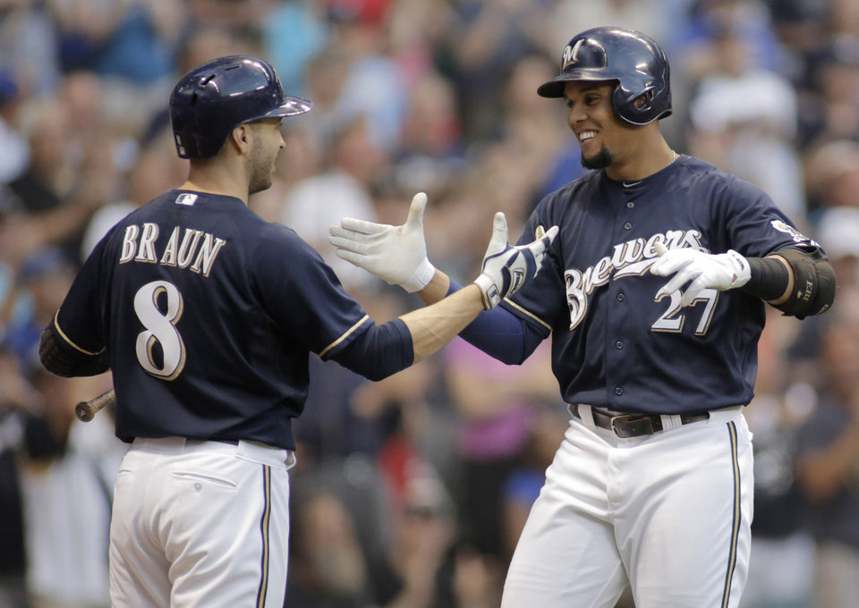 Photo - Milwaukee Brewers' Carlos Gomez, right, celebrates his home run against the Los Angeles Dodgers with Ryan Braun, left, during the sixth inning of a baseball game Saturday, Aug. 9, 2014, in Milwaukee. (AP Photo/Darren Hauck)