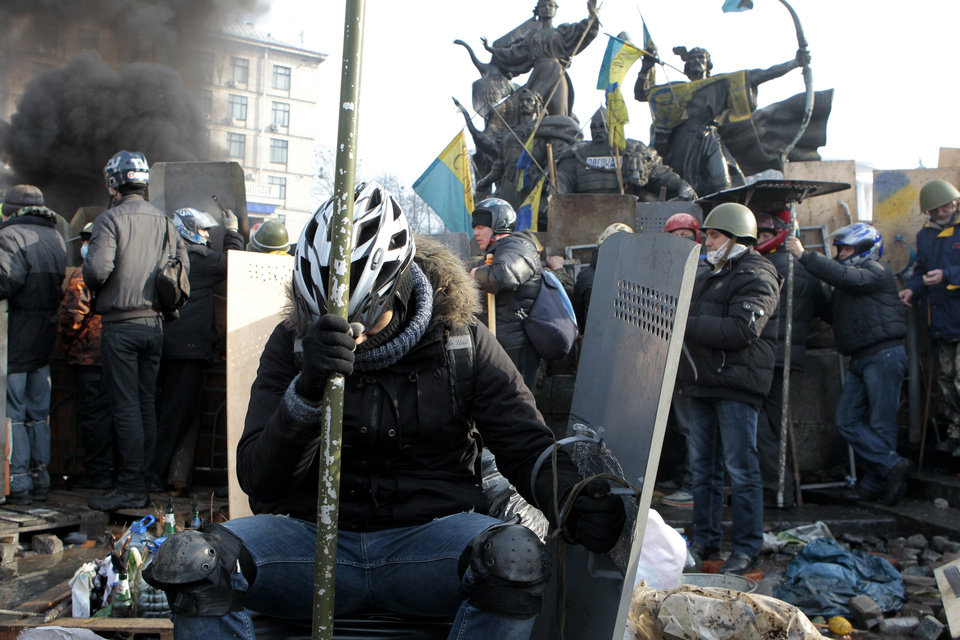 Photo - An anti-government protester relaxes during clashes with riot police in Kiev's Independence Square, the epicenter of the country's current unrest, Kiev, Ukraine, Wednesday, Feb. 19, 2014. The deadly clashes in Ukraine's capital have drawn sharp reactions from Washington, generated talk of possible European Union sanctions and led to a Kremlin statement blaming Europe and the West. (AP Photo/Sergei Chuzavkov)