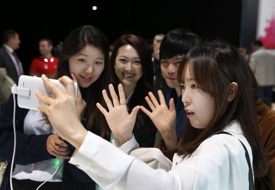 Photo - People pose for a selfie using LG's newly unveiled smartphone called the G3 at a press event in London, Tuesday, May 27, 2014. (AP Photo/Lefteris Pitarakis)
