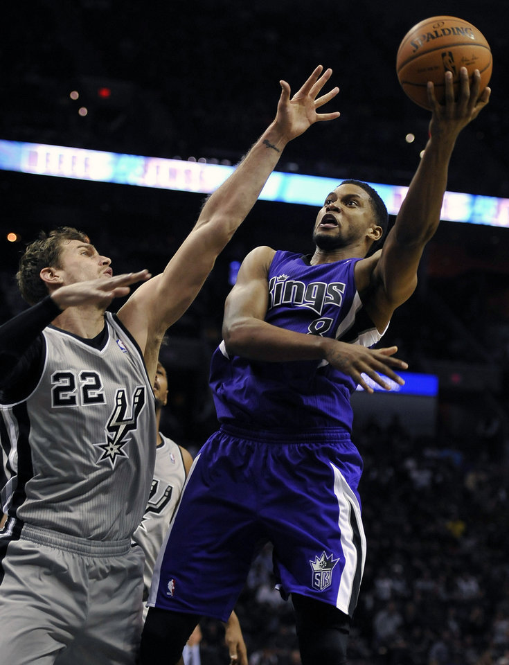 Photo - Sacramento Kings forward Rudy Gay, right, shoots against San Antonio Spurs forward Tiago Splitter during the second half of an NBA basketball game on Saturday, Feb. 1, 2014, in San Antonio. San Antonio won 95-93. (AP Photo/Darren Abate)