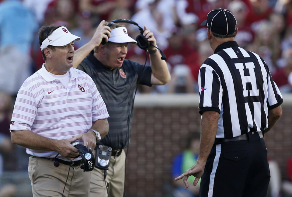 Photo - Oklahoma coach Bob Stoops, left, and associate head coach Mike Stoops, center, argue a call with an official, right, in the first quarter of an NCAA college football game against Louisiana Tech in Norman, Okla., Saturday, Aug. 30, 2014. (AP Photo/Sue Ogrocki)