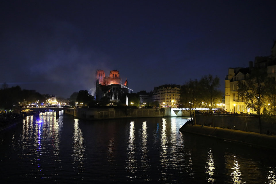 Photo - Notre Dame cathedral is seen burning in Paris, Monday, April 15, 2019. A catastrophic fire engulfed the upper reaches of Paris' soaring Notre Dame Cathedral as it was undergoing renovations Monday, threatening one of the greatest architectural treasures of the Western world as tourists and Parisians looked on aghast from the streets below. (AP Photo/Francois Mori)