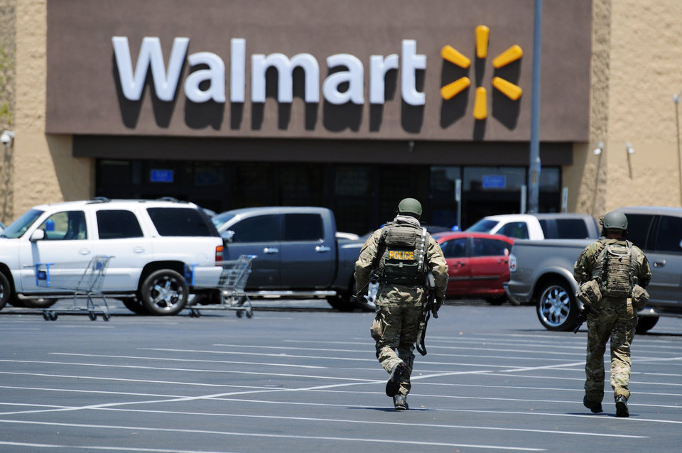 Photo - FILE - In this Sunday, June 8, 2014, file photo, Las Vegas police officers walk near the scene of a shooting in Las Vegas. At a time when shootings seem to happen almost daily, how should Americans react if someone opens fire at work, at school or at a theater or store? The Associated Press consulted experts on what to do. (AP Photo/Las Vegas Review-Journal, Eric Verduzco, File)