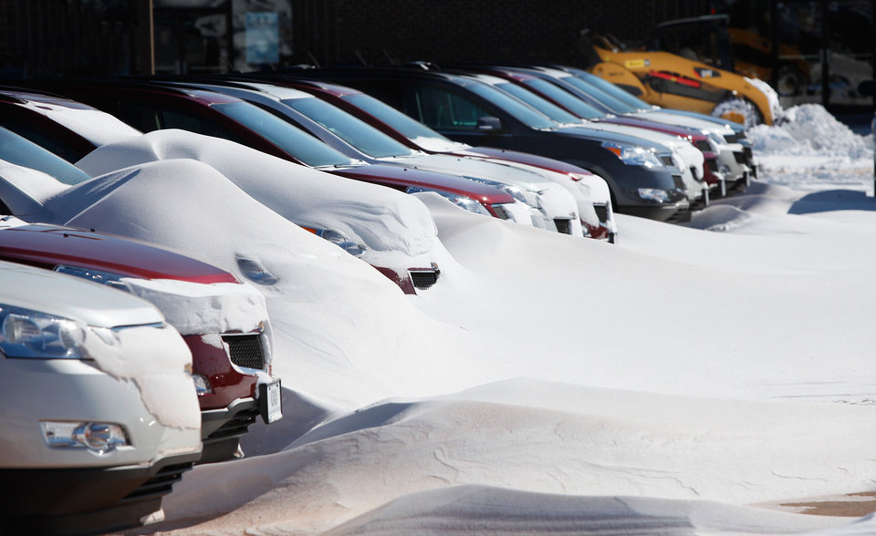 Photo - Drifts of snow covered the fronts of cars Wednesday at Bob Howard Chevrolet near Memorial Road and the Broadway Extension.Central Oklahoma residents began digging out from beneath nearly a foot of snow covering the ground Wednesday, Feb, 2, 2011, after yesterday's winter snowstorm. Photo by Jim Beckel, The Oklahoman