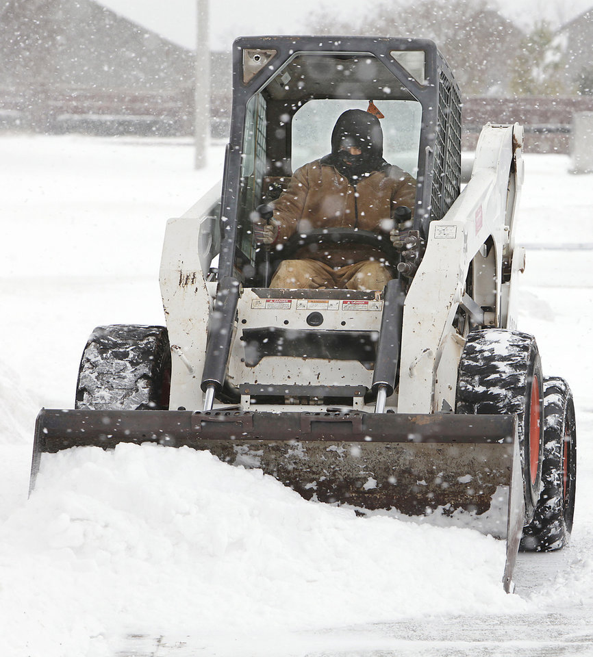 Photo - Juan Fernandez, 31, used a Bobcat Wednesday morning to help clear the drive into Oklahoma Christian University, Wednesday, February 9 , 2011. Photo by David McDaniel, The Oklahoman
