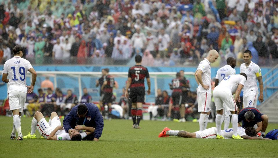 Photo - United States' Alejandro Bedoya, left, and United States' Jermaine Jones are tended to by medical personnel after colliding during the group G World Cup soccer match between the USA and Germany at the Arena Pernambuco in Recife, Brazil, Thursday, June 26, 2014. (AP Photo/Ricardo Mazalan)