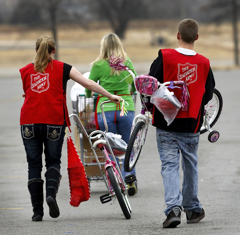 Two volunteers follow a client to her car where they will load these toys and bicycles into the vehicle. The Salvation Army and Feed the Children teamed to distribute bicycles and toys for children,  and handed out boxes of food for families at their annual distribution event Wednesday, Dec. 19, 2012. Salvation Army officials said 100 volunteers helped make the event go smoothly. The volunteers loaded bags of toys and bikes into vehicles of clients who had been pre-approved for assistance.  Many of the gifts were provided through the Salvation Army's Angel Tree program   Photo by Jim Beckel, The Oklahoman