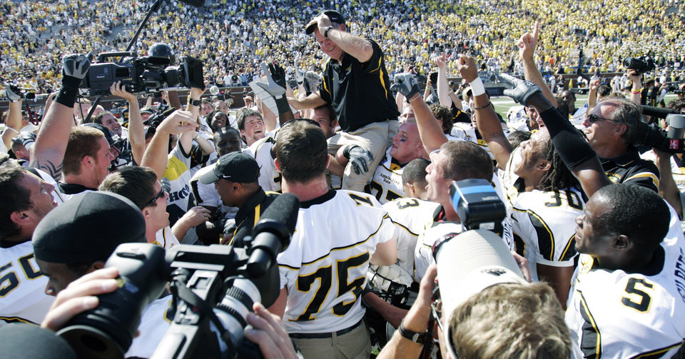 Photo -  Appalachian State coach Jerry Moore is carried off the field by his players after they upset Michigan 34-32 on Sept. 1, 2007. [AP PHOTO]