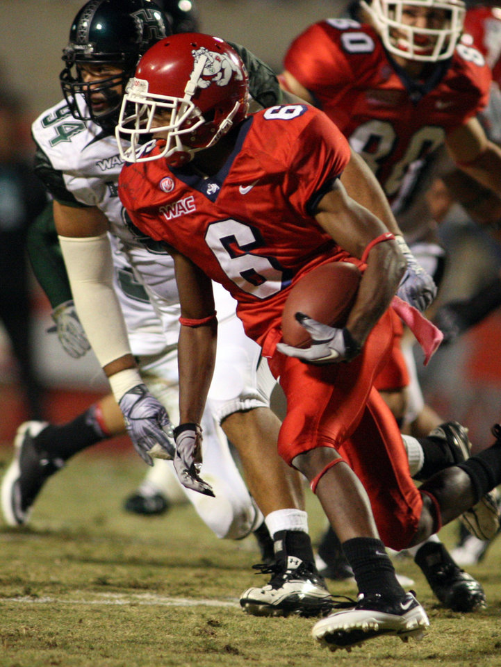 Photo - Fresno State University's Jalen Saunders runs past Hawaii's Kamalu Umu in the first half of an NCAA college football game Saturday, Oct. 9, 2010 in Fresno, Calif. (AP Photo/Gary Kazanjian) ORG XMIT: CAGK105