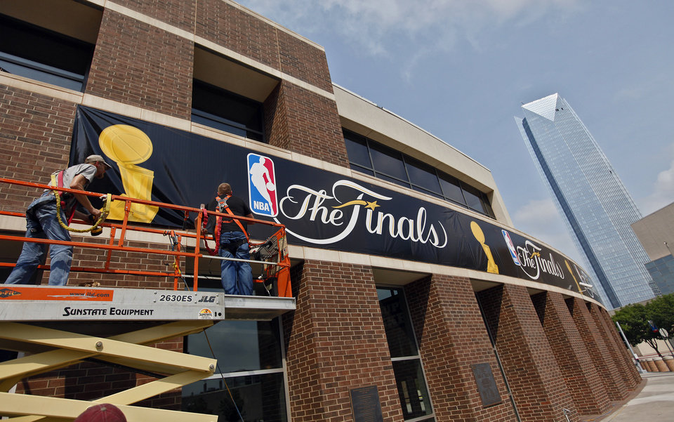Photo - Crews work to hang NBA Finals banners around the Chesapeake Energy Arena on Monday, June 11, 2012, in Oklahoma City, Okla. Photo by Chris Landsberger, The Oklahoman