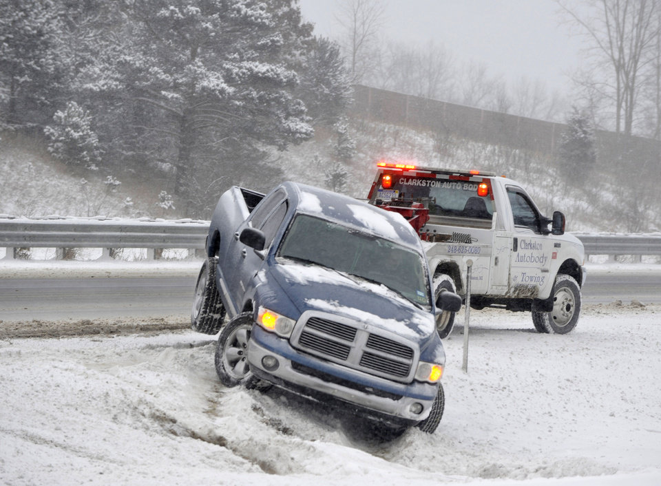 Photo - A pickup trucked is pulled out of the snow along southbound  I-75 near  Dixie Highway by a tow truck in Clarkston, Mich., Thursday, Jan. 2, 2014. Roads were slippery and snow-covered in Detroit and its suburbs for the Thursday morning commute.  (AP Photo/Detroit News,  Charles V. Tines) DETROIT FREE PRESS OUT; HUFFINGTON POST OUT, MADATORY CREDIT