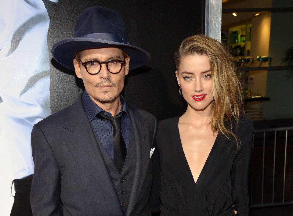 Photo - FILE - This Feb. 12, 2014 file photo shows Johnny Depp, left, and Amber Heard at the US premiere of