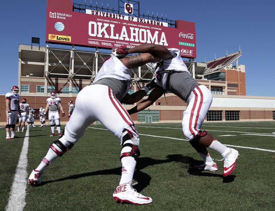 Photo - Charles Walker, left and Mike Onuoha go through drills as the University of Oklahoma Sooners (OU) begin spring practice on fields next to Gaylord Family-Oklahoma Memorial Stadium in Norman, Okla., on Tuesday, March 11, 2014. Photo by Steve Sisney, The Oklahoman