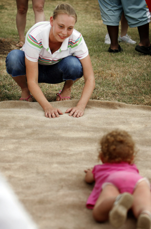 Amber Ramos coaxes daughter Aubrey, 23 months, in the baby crawl/walk competition at the Norman Independence Day Celebration at Reaves Park in Norman, Okla., on Saturday, July 4, 2009.     Photo by Steve Sisney, The Oklahoman