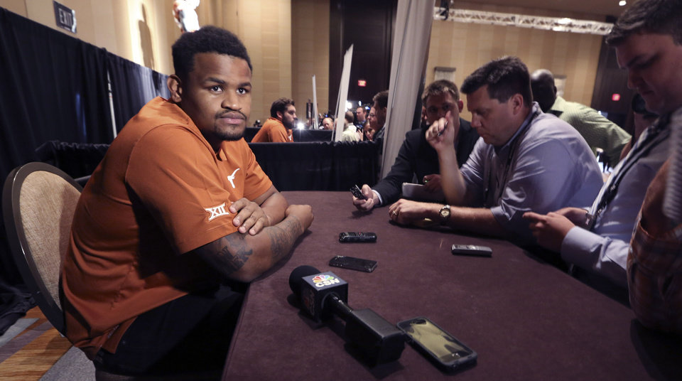 Photo - Texas defensive end Cedric Reed listens to reporters questions during the NCAA college Big 12 Conference football media days in Dallas, Tuesday, July 22, 2014. (AP Photo)