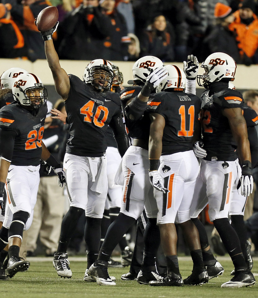 Photo - The OSU defense celebrates a fumble recovery by Shaun Lewis (11) in the third quarter during a college football game between the Oklahoma State University Cowboys (OSU) and the Baylor University Bears (BU) at Boone Pickens Stadium in Stillwater, Okla., Saturday, Nov. 23, 2013. OSU won, 49-17. Photo by Nate Billings, The Oklahoman