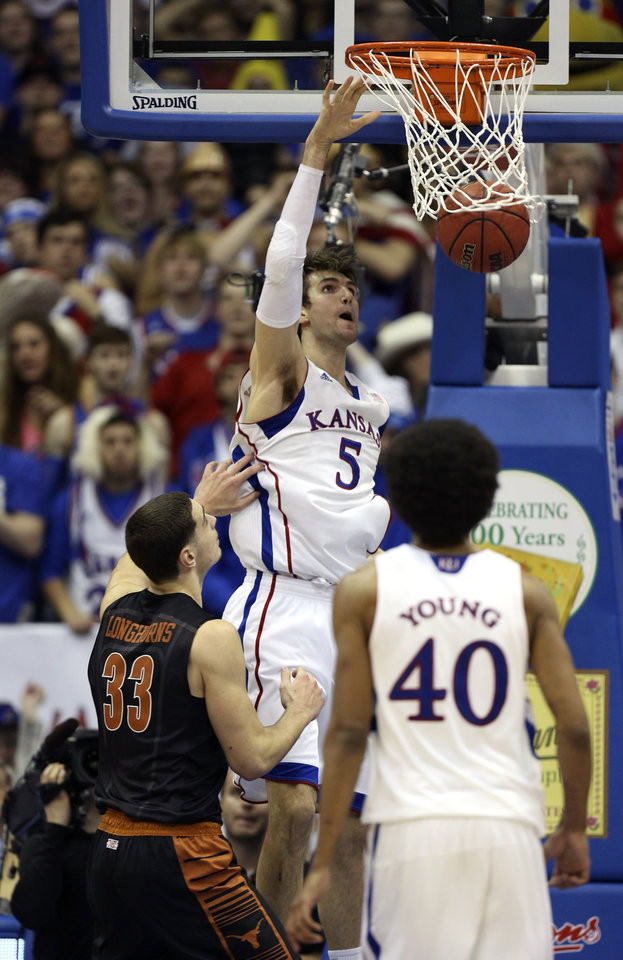 Kansas' Jeff Withey (5) dunks the ball past Texas' Ioannis Papapetrou (33) during the second half of an NCAA college basketball game Saturday, Feb. 16, 2013, in Lawrence, Kan. Kansas won 73-47. (AP Photo/Ed Zurga)