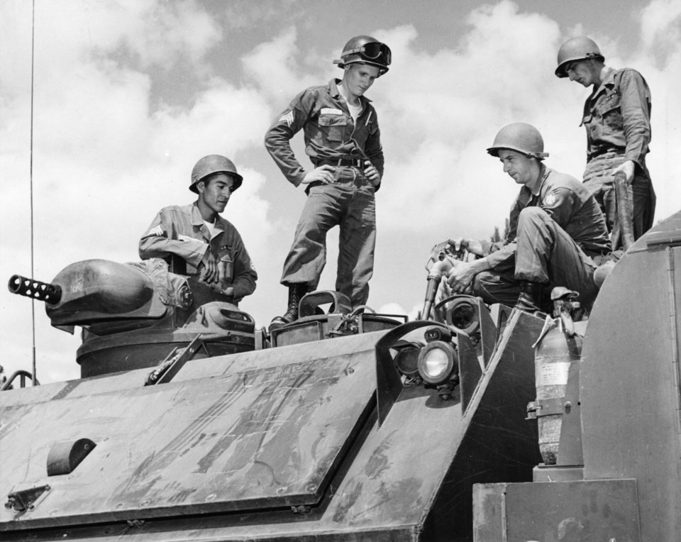 Photo - FILLING 'ER UP is no little chore for these four Thunderbirds of the 45th Infantry Division in summer camp at North Fort Polk, La.  The M-48 they are filling holds about 200 gallons of gas and gets about 2 1/2 gallons to the mile.  Left to right are Sgt. Delbert Toquothty  and Sgt. Douglas Taylor, both of Walters, and Specialists Bob Reynolds, 636 SW 2, and Frank Lumley, 744 SW 28.  Staff photo by George Tapscott.  Staff 2016/1962 in The Daily Oklahoman(E).