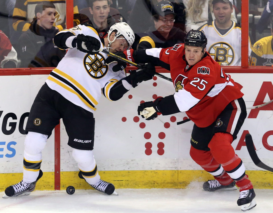 Ottawa Senators' Chris Neil (25) and Boston Bruins' Aran Johnson (45) fight for possession of the puck during the first period of their NHL hockey game, Thursday, March 21, 2013, in Ottawa, Ontario. (AP Photo/The Canadian Press, Fred Chartrand)