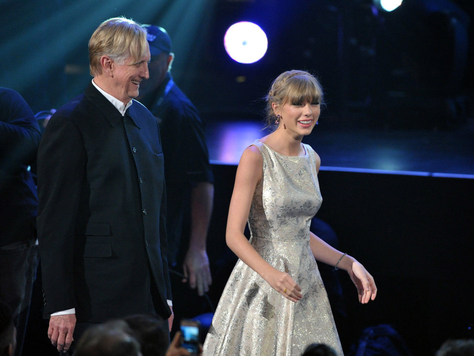 Photo - T Bone Burnett, left, and Taylor Swift, right walk to the stage to accept the award for song written for visual media for