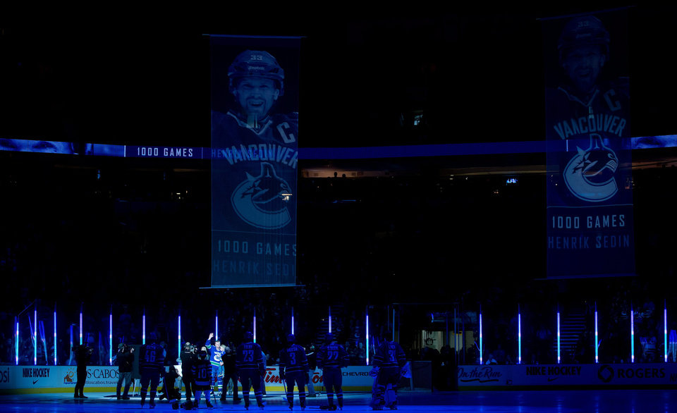 Photo - Vancouver Canucks' Henrik Sedin, of Sweden, waves to the crowd as he's honoured for playing 1,000 NHL games before the NHL hockey game against the Buffalo Sabres in Vancouver, British Columbia, on Sunday March 23, 2014. (AP Photo/The Canadian Press, Darryl Dyck)