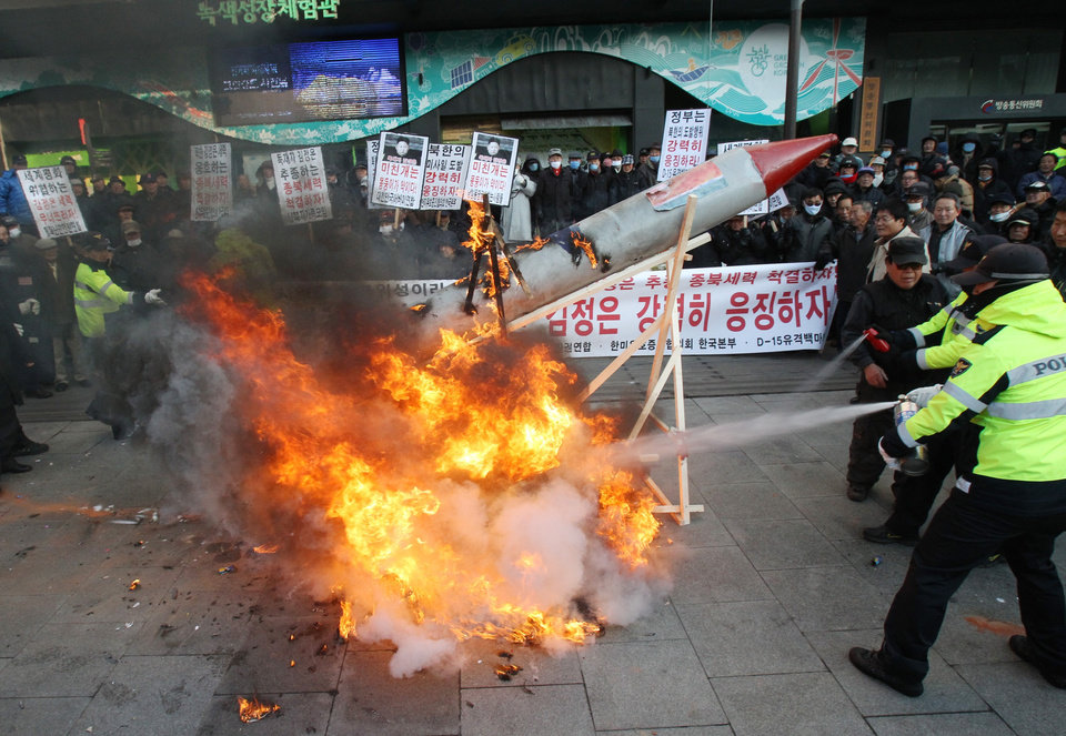 South Korean protesters burn a mock rocket as police officers spray fire extinguishers during a rally denouncing North Korea's rocket launch in Seoul, South Korea, Wednesday, Dec. 12, 2012.  North Korea successfully fired a long-range rocket on Wednesday, defying international warnings as the regime of Kim Jong Un took a giant step forward in its quest to develop the technology to deliver a nuclear warhead.  (AP Photo/Ahn Young-joon) ORG XMIT: SEL106