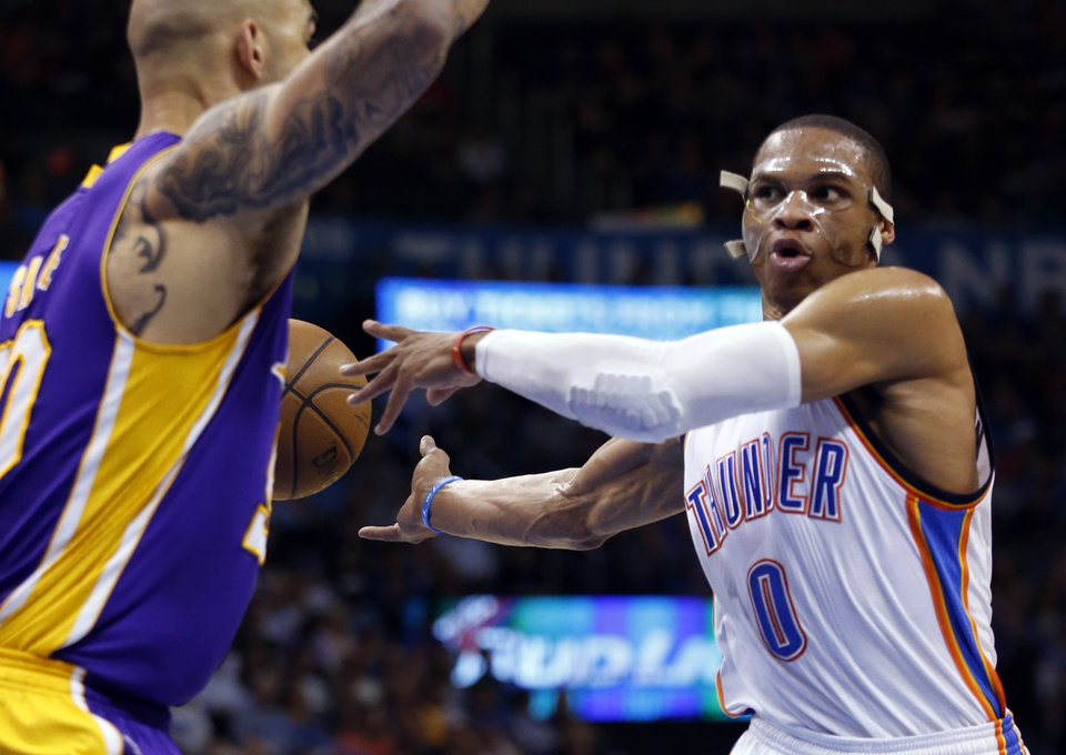 Photo - Oklahoma City's Russell Westbrook (0) passes behind Los Angeles' Robert Sacre (50) for an assist during the NBA basketball game between the Oklahoma City Thunder and the Los Angeles Lakers at Chesapeake Energy Arena on March 24, 2015 in Oklahoma City, Okla. Photo by Steve Sisney, The Oklahoman